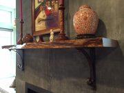 A decorative shelf held by black hand-forged iron brackets by Shoreline Ornamental Iron